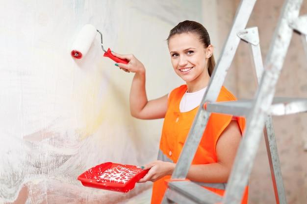 Pittore vernicia parete con rullo