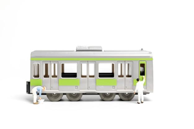 Pittori che verniciano un treno su fondo bianco