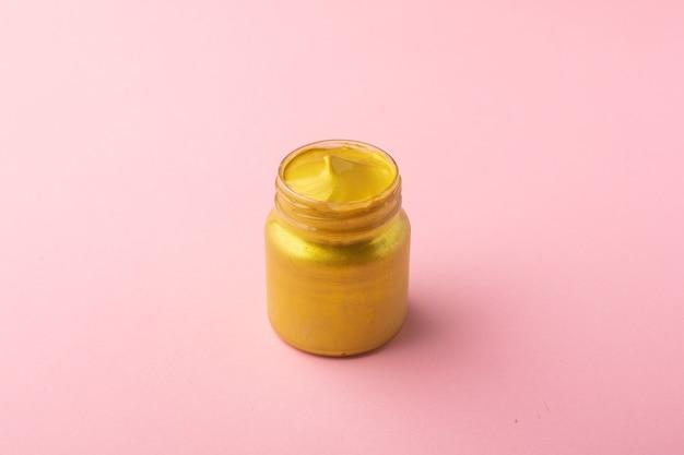 Pittura acrilica oro con un pennello su sfondo rosa, semplice composizione pastello