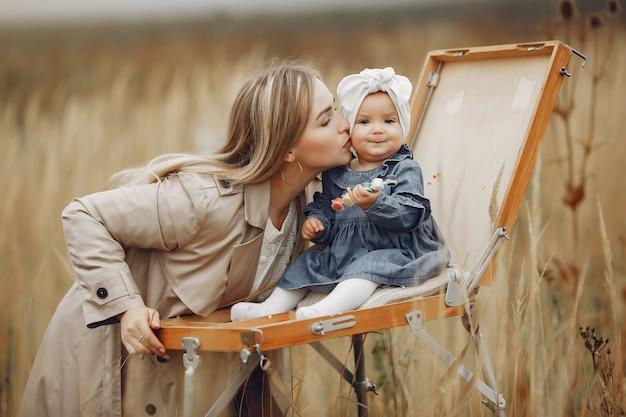 Pittura della bambina in un campo di autunno con la madre
