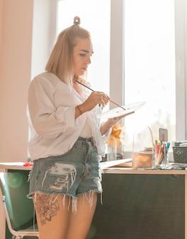Pittura della donna con acquerello in studio