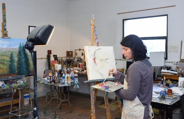 Pittura della donna in uno studio di pittura