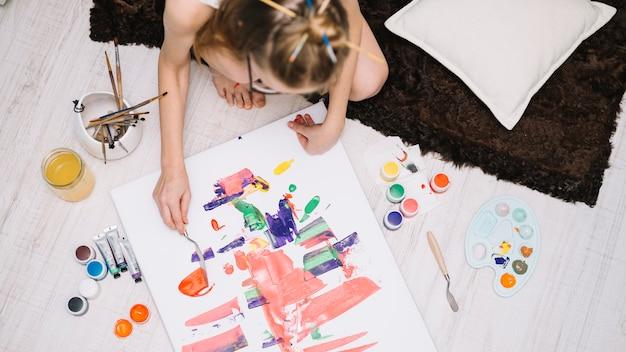 Pittura della ragazza con gouache su carta sul pavimento