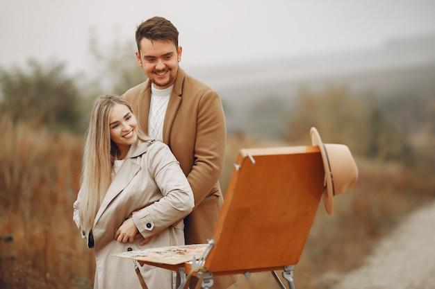 Pittura elegante delle coppie in un campo di autunno