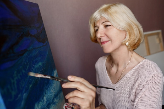 Pittura femminile matura felice su tela a casa