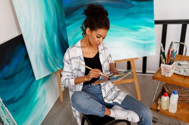 Pittura femminile professionale dell'artista sulla tela in studio. donna pittrice nel suo spazio di lavoro.