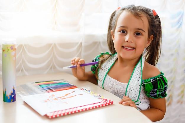 Pittura sorridente del bello bambino del tipo di angelo. bambina affascinante che disegna l'immagine per suo padre, preparando la sorpresa di compleanno per lui.