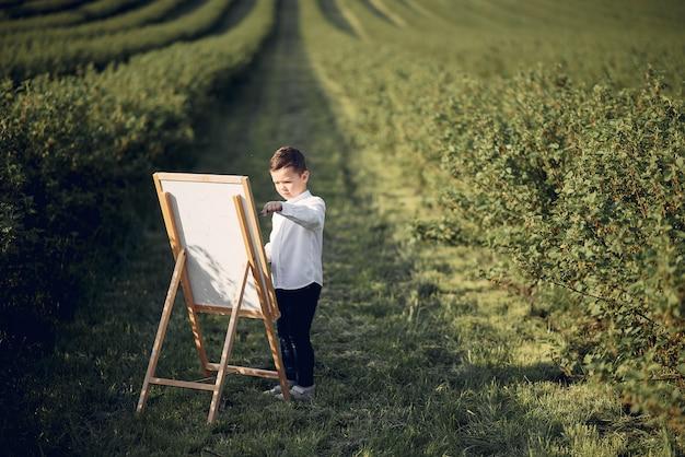 Pittura sveglia del ragazzino in un parco
