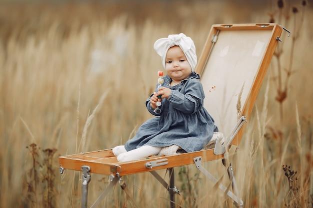 Pittura sveglia della bambina in un campo di autunno