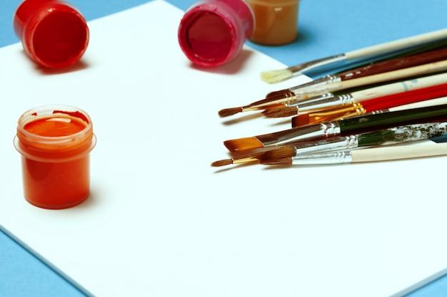 Pitture e spazzole dell'acquerello su fondo blu luminoso