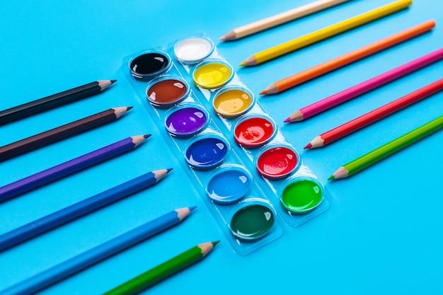 Pitture luminose a guazzo per disegno situate al centro su un blu attorno alle matite colorate brillanti stese. avvicinamento.