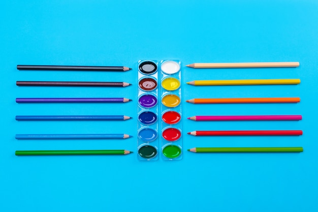 Pitture luminose a guazzo per disegno situate al centro su un blu con matite luminose intorno alle matite sparse. di nuovo a scuola. avvicinamento.