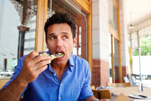Più vecchio uomo bello mangiare la pizza al ristorante all'aperto