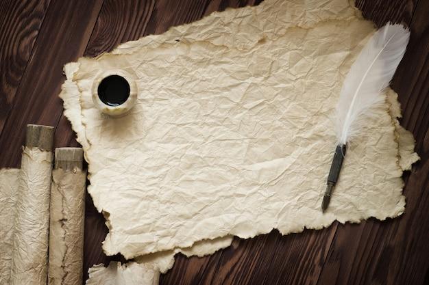 Piuma bianca e antica pergamena su tavola marrone