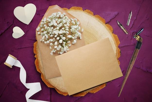 Piuma calligrafica, si trova vicino a un cerchio di legno con un cuore di carta bianca. biglietto di auguri per san valentino