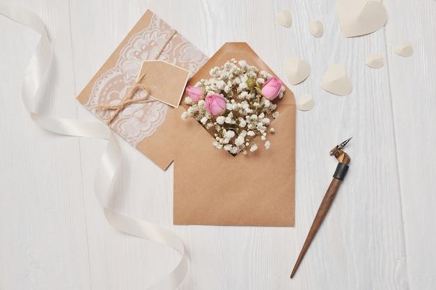 Piuma calligrafica una busta con fiori e una lettera, biglietto di auguri