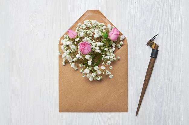 Piuma calligrafica una busta con fiori e una lettera, cartolina d'auguri per san valentino
