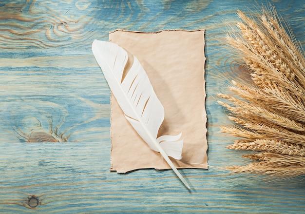 Piuma d'annata della pergamena delle orecchie del grano della segale sul bordo di legno