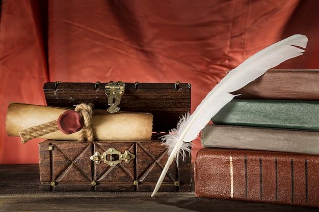 Piuma vicino al rotolo sigillato nella vecchia cassa e libri vintage