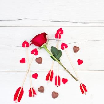 Piume di ornamento su bacchette con cuoricini vicino a fiori e caramelle
