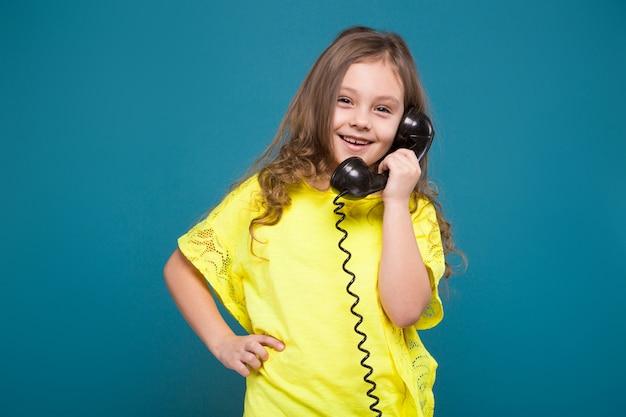 Piuttosto, bambina in t-shirt con capelli castani tenere il telefono