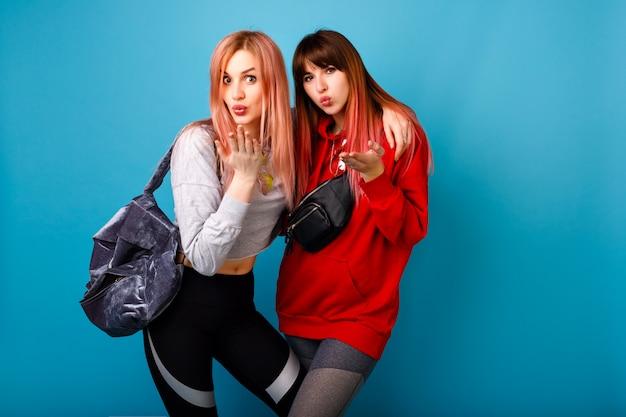 Piuttosto giovane coppia di ragazze migliori amiche che inviano baci d'aria, indossano abiti e borse per lo sport fitness, stile di vita sano, muro blu.