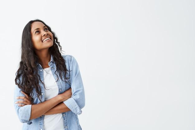 Piuttosto giovane donna afro-americana bruna con lunghi capelli ondulati guardando in alto e lontano, sinceramente sorridente, tenendo le braccia conserte sulla camicia di jeans. concetto di persone ed emozioni positive.