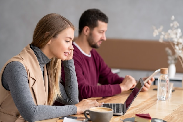 Piuttosto giovane donna in abbigliamento casual seduto da un tavolo di legno davanti al display del laptop e comunica tramite chat video