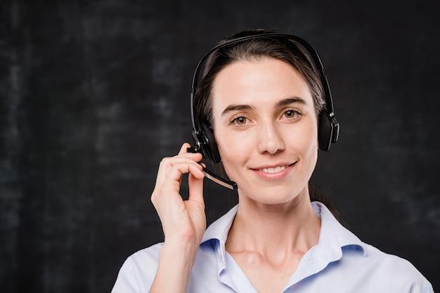 Piuttosto giovane imprenditrice sorridente con auricolare a parlare con i clienti davanti alla telecamera su sfondo nero