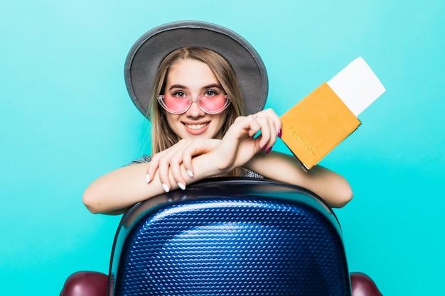 Piuttosto giovane signora adolescente tiene i suoi documenti del passaporto con il biglietto nelle sue mani e la valigia blu isolata sulla parete verde dello studio