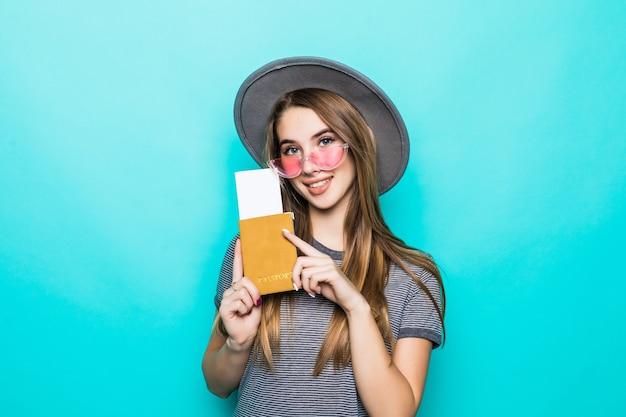 Piuttosto giovane signora adolescente tiene i suoi documenti del passaporto con il biglietto nelle sue mani isolate sulla parete verde dello studio