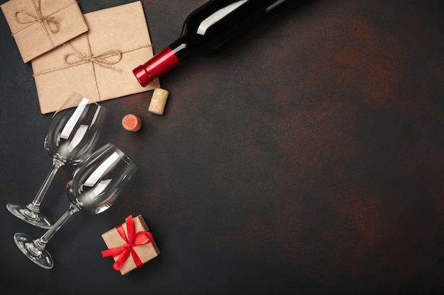Pizza a forma di cuore con mozzarella, salsiccia, bottiglia di vino, due bicchiere da vino, confezione regalo su sfondo arrugginito