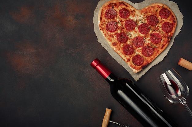Pizza a forma di cuore con mozzarella, salsiccia con una bottiglia di vino e wineglas su sfondo arrugginito.