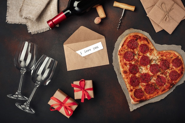 Pizza a forma di cuore con mozzarella, salsiccia e bottiglia di vino, cavatappi, bicchiere da vino. su sfondo arrugginito