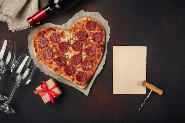 Pizza a forma di cuore con mozzarella, salsiccia e bottiglia di vino, cavatappi, bicchiere da vino.