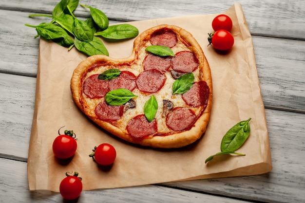Pizza a forma di cuore su un tavolo di legno