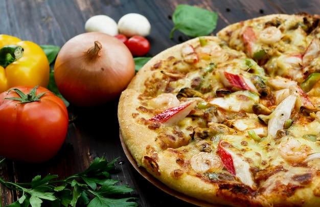 Pizza ai frutti di mare e ingredienti, verdure da decorare come l'aglio pomodoro peperoncino
