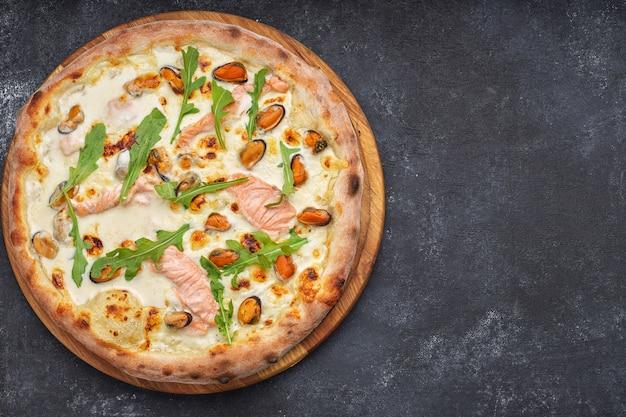 Pizza ai frutti di mare, marinara, di mare, con salmone, cozze e rucola, su una tavola di legno, contro un tavolo scuro