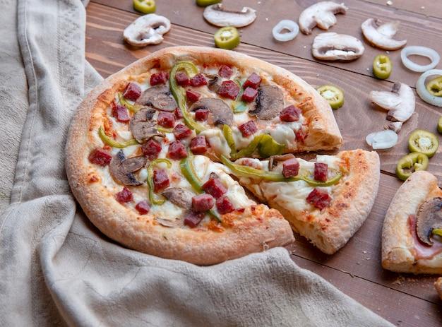 Pizza ai funghi affettata sul tavolo di legno
