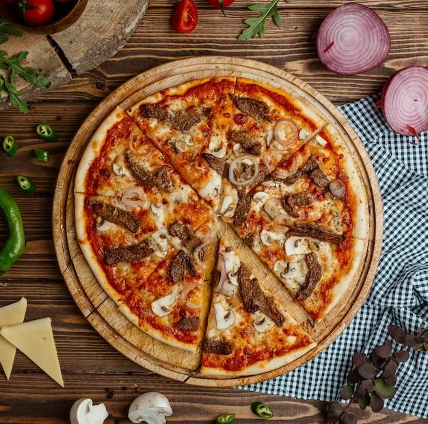 Pizza ai funghi con cipolla e formaggio sul piatto di legno