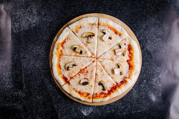 Pizza ai funghi, formaggio, salsa di pomodoro tagliata a fette.