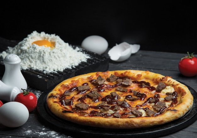 Pizza ai peperoni classica con farina e uovo sul tavolo