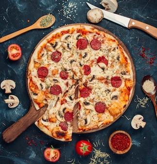 Pizza ai peperoni con funghi sul tavolo