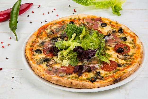 Pizza ai peperoni con mozzarella, salame, pomodori, pepe, spezie e basilico fresco. pizza italiana