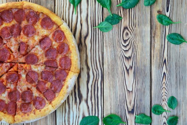 Pizza ai peperoni con spinaci su un fondo di legno