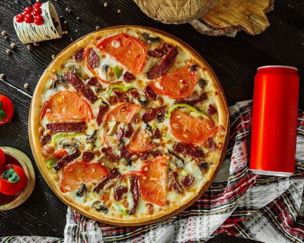 Pizza ai peperoni condita con fette di pomodoro, pepe e funghi