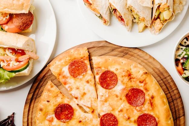Pizza ai peperoni, panini, shaurma sul tavolo bianco.