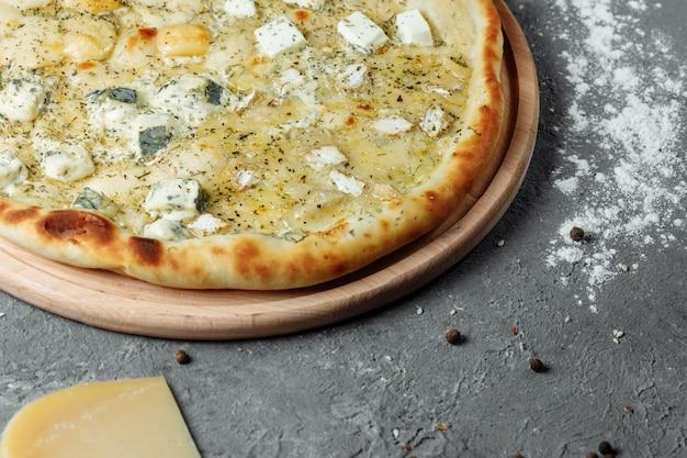 Pizza ai quattro formaggi, pizza italiana. pizza ripiena di quattro varietà di formaggio su uno sfondo grigio.
