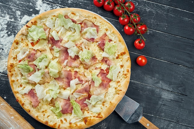 Pizza al forno con lattuga, crostini, besciamella e pollo. pizza caesar su un tavolo di legno nero in una composizione con ingredienti. vista dall'alto