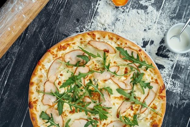 Pizza al forno con pollo affumicato, besciamella e formaggio fuso su una tavola di legno nera in una composizione con ingredienti. vista dall'alto